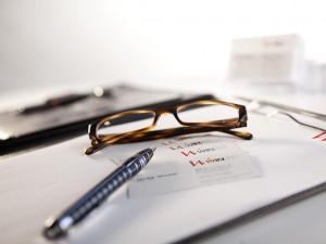 nahaufnahme-stillleben-unternehmensdarstellung-beratung-brille-notizen-kundenkontakt
