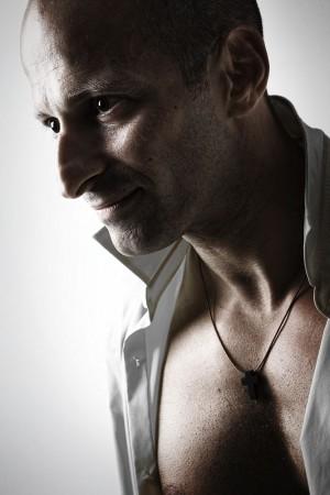 mann-markant-offenes-hemd-lächeln-interessantes-licht-studio-portrait