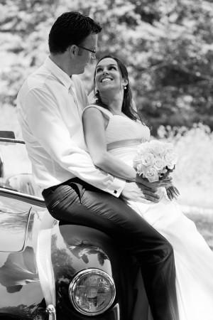 Hochzeitsfotograf, Brautpaar an Auto angelehnt schwarz-weiss