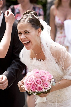 Braut lachend mit Strauss