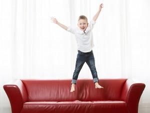 Kinder Fotoshooting, springend auf rotem Sofa