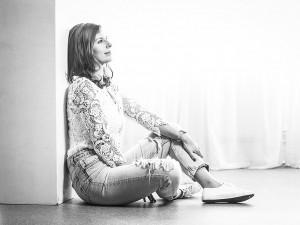 Schwarz Weiß Portrait einer Frau, angelehnt an einer Wand und träumend