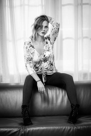 Portrait einer Frau sitzend auf einem Sofa und cooler Pose